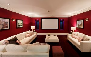 a cinema room in an expensive new home with large comfortable cream coloured settees, silk cushions and a foot stool. On either side of the screen are recessed windows with electronic blinds (lowered) and alcove lights. The pictures on the wall are the photographer's.