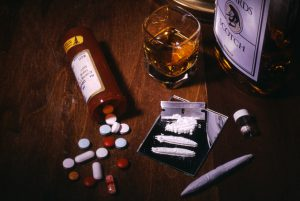Tableau of drugs- pills, coke, marijuana, and alcohol.